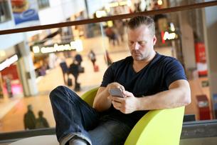 Germany, Hamburg, Mature man sitting in airport hall and using telephoneの写真素材 [FYI02856160]