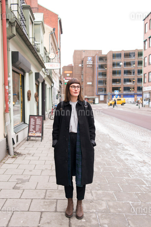 Sweden, Skane, Malmo, Young woman standing on sidewalkの写真素材 [FYI02856165]