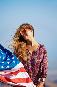 USA, California, Young blonde woman holding US flagの写真素材 [FYI02856168]