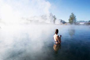 A woman bathing in The Secret Lagoon in Icelandの写真素材 [FYI02856192]