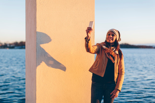 Woman taking selfie by the seaの写真素材 [FYI02856197]
