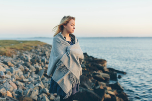 A young woman wrapped in a shawl looking out to seaの写真素材 [FYI02856207]