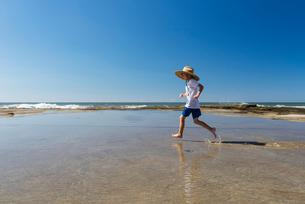 Australia, Queensland, Sunshine Coast, Moffat Beach, Boy (6-7) in straw hat running through water onの写真素材 [FYI02856208]