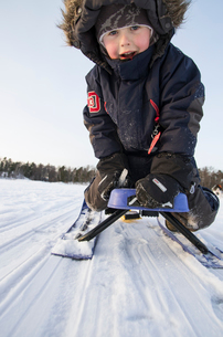 Finland, Nyland, Drumso, Smiling boy (4-5) sitting on sledの写真素材 [FYI02856234]