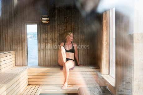 Sweden, Vastra Gotaland, Stromstad, Young woman relaxing in saunaの写真素材 [FYI02856237]