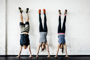 Germany, Young women and man practicing handstand in gymの写真素材 [FYI02856240]