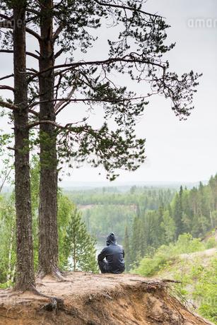 Man wearing a hoodie sitting under treesの写真素材 [FYI02856247]