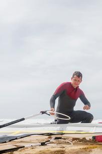 Portugal, Lisbon, Praia do Guincho, Man preparing windsurfing board on beachの写真素材 [FYI02856251]
