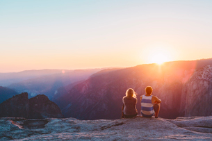 USA, California, Yosemite National Park, Taft Point, Man and woman watching sunset in mountainsの写真素材 [FYI02856267]