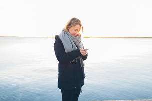 Woman holding a smart phone by the seaの写真素材 [FYI02856274]