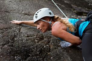 Sweden, Ostergotland, Vaderstad, Woman climbing rockの写真素材 [FYI02856282]