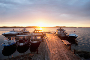 Sweden, Stockholm, Sodermanland, Dalaro, Boats by pier at sunsetの写真素材 [FYI02856287]