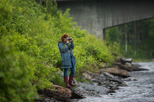 Woman taking photographs by riverの写真素材 [FYI02856288]