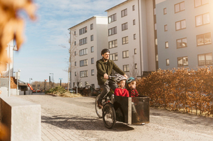 Man cycling with his sons in Stockholmの写真素材 [FYI02856300]