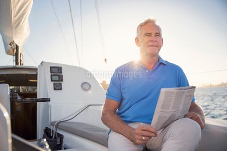 Australia, New South Wales, Sydney Harbor, Portrait of senior man holding newspaper on motorboatの写真素材 [FYI02856314]