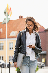 Young woman looking at her cell phone in Solvesborg, Swedenの写真素材 [FYI02856316]