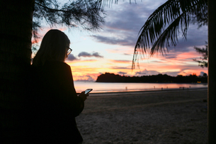 Woman on smart phone at beach in Ko Lanta, Thailandの写真素材 [FYI02856321]
