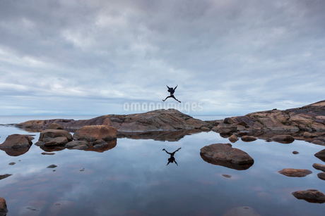 Woman jumping on rock by a lake in Vasterbotten, Swedenの写真素材 [FYI02856324]