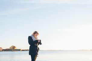 Woman holding a camera by the seaの写真素材 [FYI02856326]