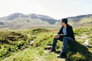 Man sits on a hill in Inner Hebrides, Scotlandの写真素材 [FYI02856329]