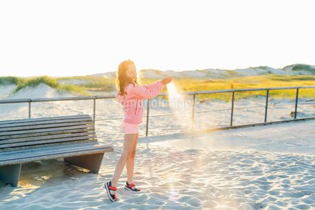 Germany, Schleswig-Holstein, Kreis Nordfriesland, Sankt Peter-Ording, Girl (10-11) pouring sand on bの写真素材 [FYI02856335]