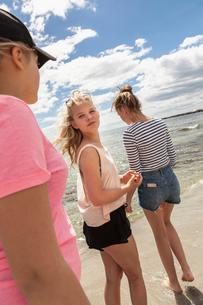 Sweden, Blekinge, Solvesbor, Torso, Teenage girls (14-15) standing on beachの写真素材 [FYI02856342]