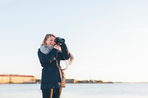 Woman taking photograph by seaの写真素材 [FYI02856348]