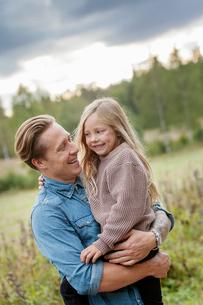 Finland, Uusimaa, Raasepori, Karjaa, Father holding his daughter (6-7)の写真素材 [FYI02856349]