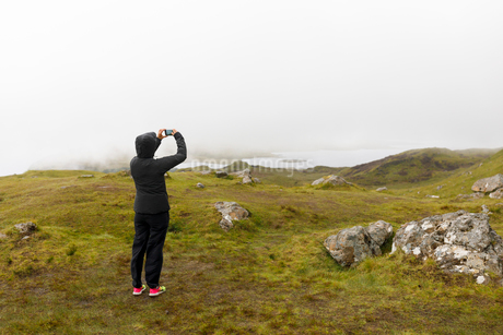 Woman taking photograph of Old Man of Storr through fog on Isle of Skye, Scotlandの写真素材 [FYI02856361]