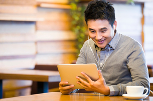 Young man enjoying videos in digital tablet in coffee shopの写真素材 [FYI02856365]