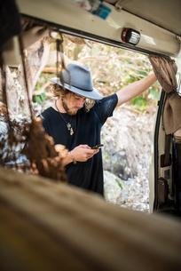 Australia, Queensland, Sunshine Coast, Noosa, Alexandria Bay, Young man using smart phoneの写真素材 [FYI02856379]