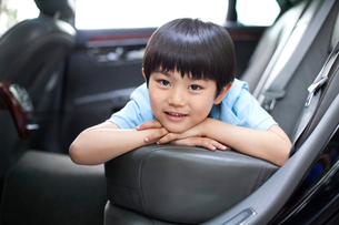 Happy boy lying in car back seatの写真素材 [FYI02856382]
