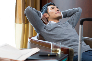 Young businessman resting in hotel roomの写真素材 [FYI02856388]