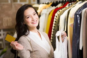 Young woman showing credit card in clothing storeの写真素材 [FYI02856389]