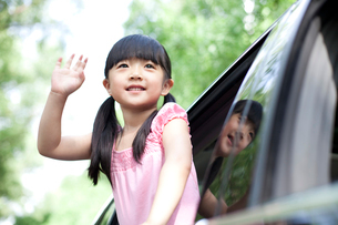 Cheerful girl leaning out of car window and wavingの写真素材 [FYI02856397]