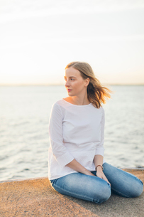 Young woman sitting near the sea in Karlskrona, Swedenの写真素材 [FYI02856403]