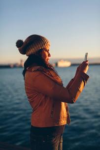 Woman holding a smart phone by the seaの写真素材 [FYI02856408]
