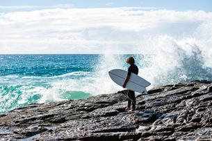 Australia, Queensland, Sunshine Coast, Noosa, Alexandria Bay, Surfer with surfboard looking at wavesの写真素材 [FYI02856410]