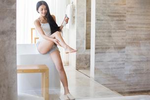 Young woman applying moisturizer to legの写真素材 [FYI02856412]