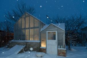 Sweden, Sodermanland, Stigtomta, Exterior of illuminated greenhouse in snowの写真素材 [FYI02856423]