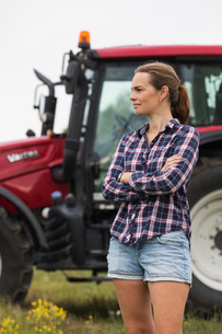 Agricultural worker standing in front of tractorの写真素材 [FYI02856433]