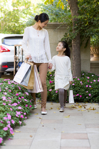 Mother and daughter walking together with shopping bagsの写真素材 [FYI02856446]