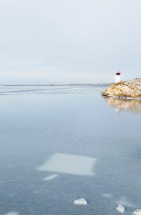 Sweden, Bohuslan, Orust, Mollosund, Lighthouse by frozen seaの写真素材 [FYI02856447]