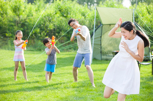 Happy young family playing squirt gunsの写真素材 [FYI02856470]