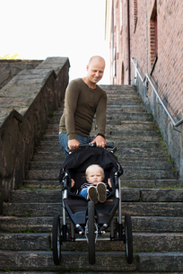 Sweden, Gotaland, Vastra, Stay at home dad pushing stroller with son (12-17 months)の写真素材 [FYI02856480]