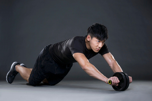 Young man exercising with Ab wheelの写真素材 [FYI02856485]