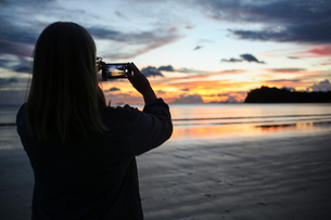 Woman taking photograph of beach during sunset in Ko Lanta, Thailandの写真素材 [FYI02856489]