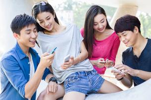 Young friends looking at smart phonesの写真素材 [FYI02856505]