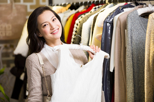 Young woman shopping in clothing storeの写真素材 [FYI02856508]