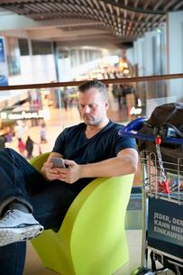 Germany, Hamburg, Mature man sitting at airport hall and using telephoneの写真素材 [FYI02856521]